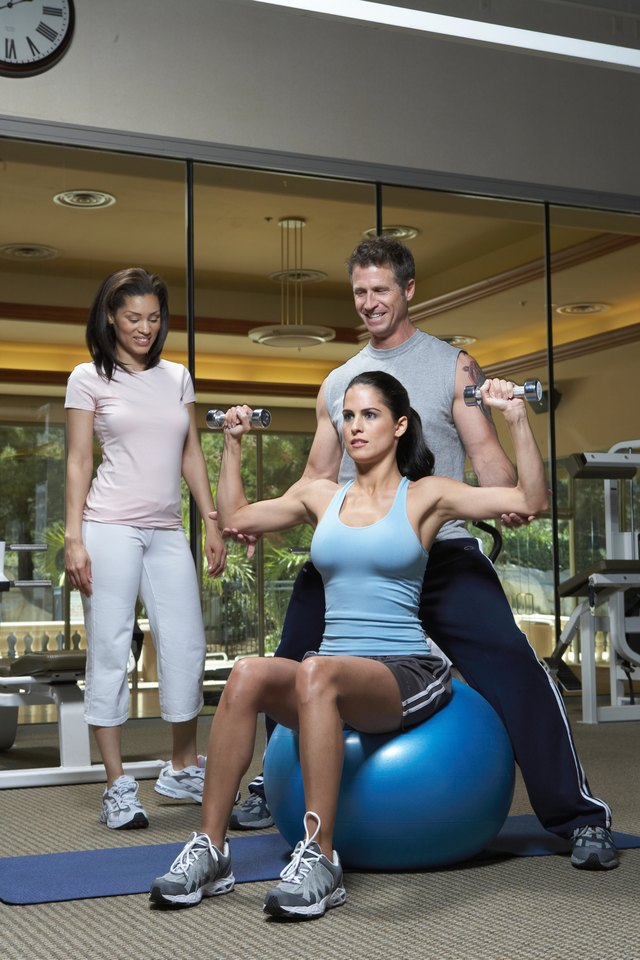Two women with instructor in gym, holding dumbbell