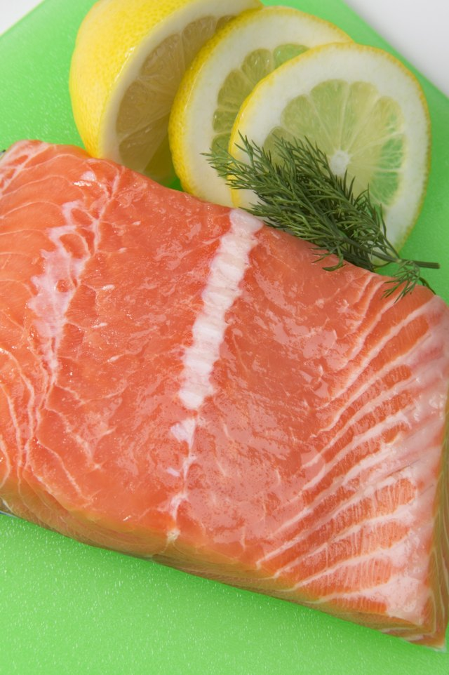 Salmon fillet on plastic cutting board with garnishes