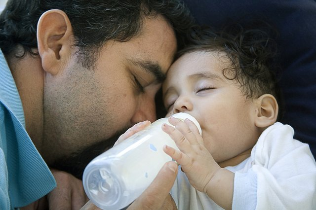 Close-up of a mature man feeding his baby with a bottle