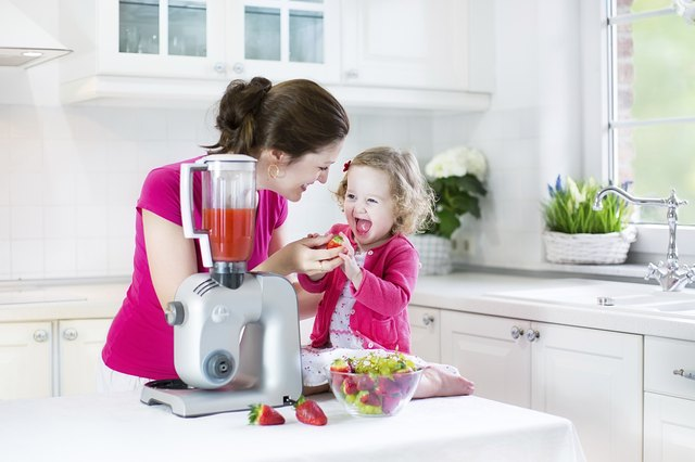 Laughing toddler girl and beautiful mother in sunny white kitchen