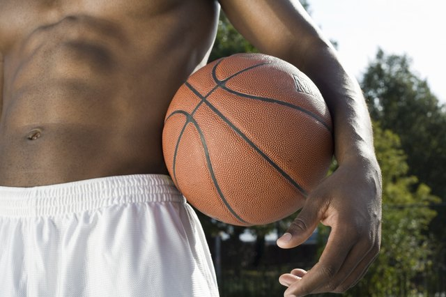 A man holding a basketball, midsection