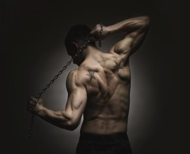 Rear view of muscular sports man stretching out over dark concrete background