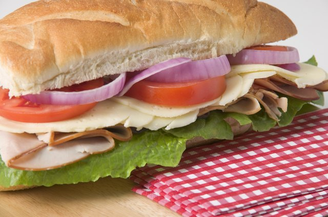 Sub sandwich on wooden cutting board with napkins