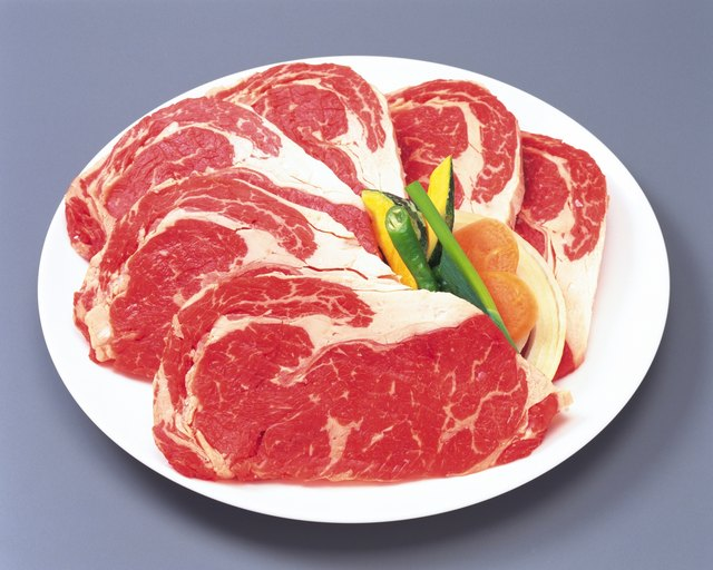 Sirloin steaks with vegetables on plate, high angle view, close up