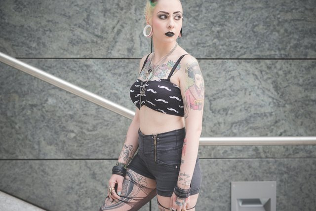 Portrait of young female tattooed punk on subway stairs