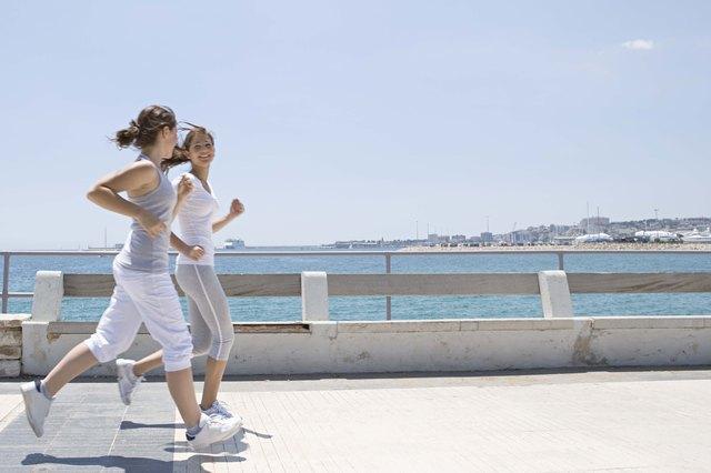 Teenage girls running on sidewalk by ocean