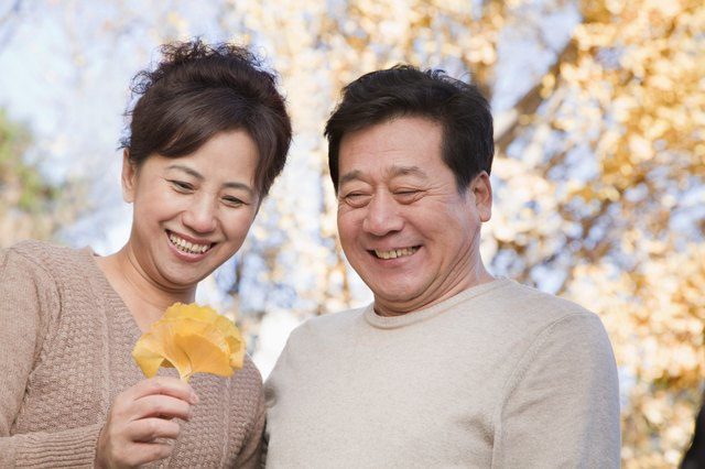 Mature Couple Looking at the Leaf in the Park