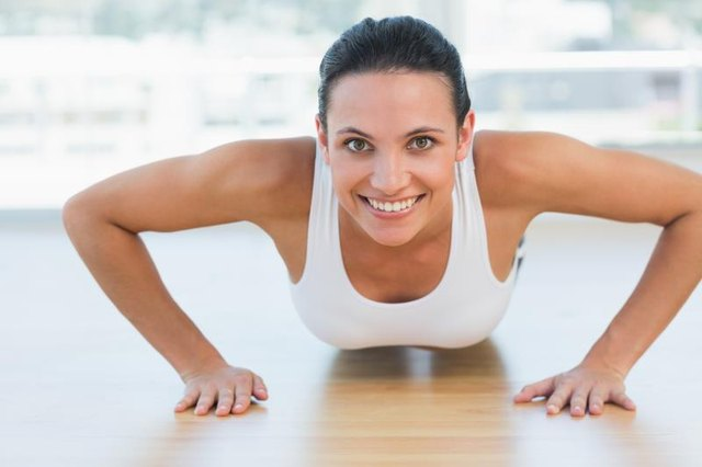 A fit woman does push-ups.