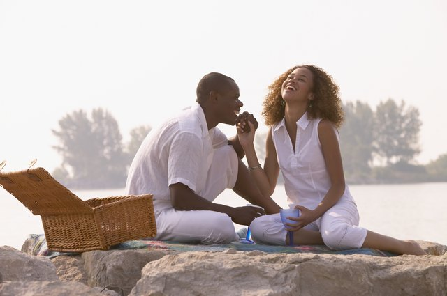 African couple having picnic on rocks