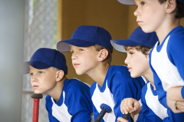 Young baseball players sitting in dugout
