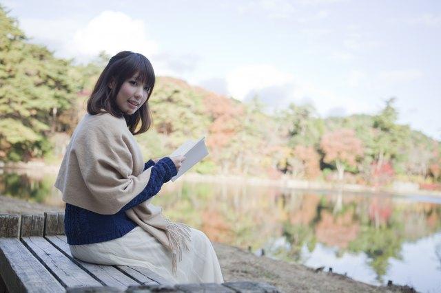 Japanese woman reading next to a lake