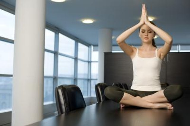 Woman doing yoga on conference table
