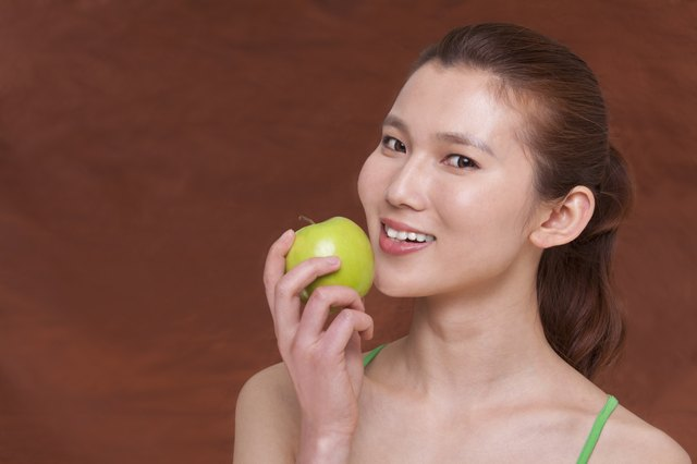 Young woman holding a apple and getting ready to take a bite, looking at camera, studio shot