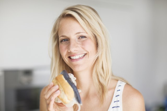 Portrait of mid adult woman holding fish sandwich