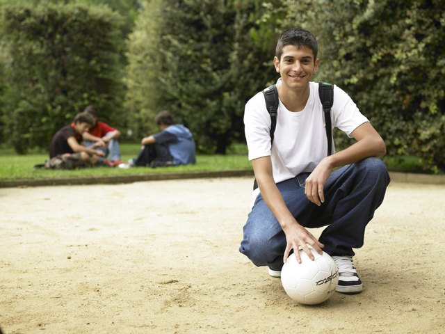 Teenage boy (15-17) kneeling with soccer ball at park