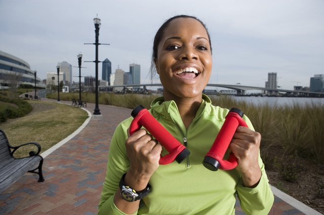 Portrait of a young woman in sports clothing jogging on walkway