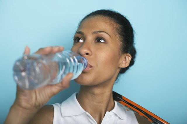 Female tennis player drinking water