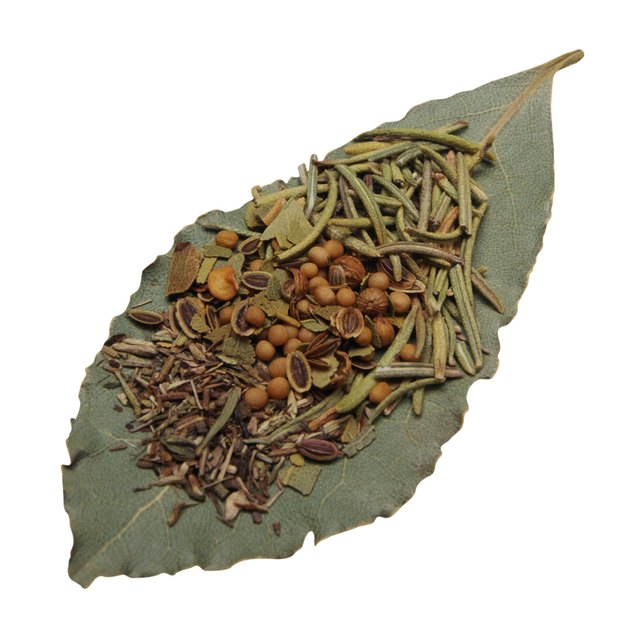 Assorted dried herbs and spices on bay leaf