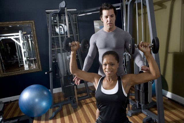 Trainer instructing a young woman with sports equipment in the gym