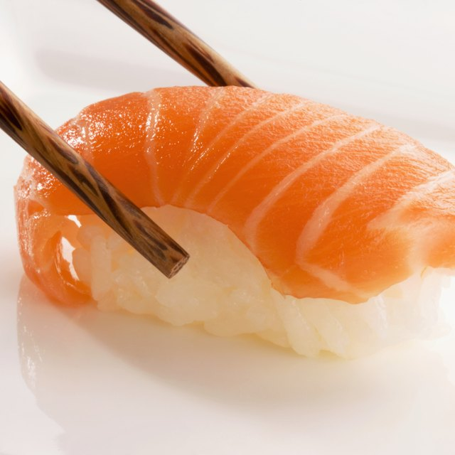 Close-up of Nigiri sushi with salmon held between chopsticks