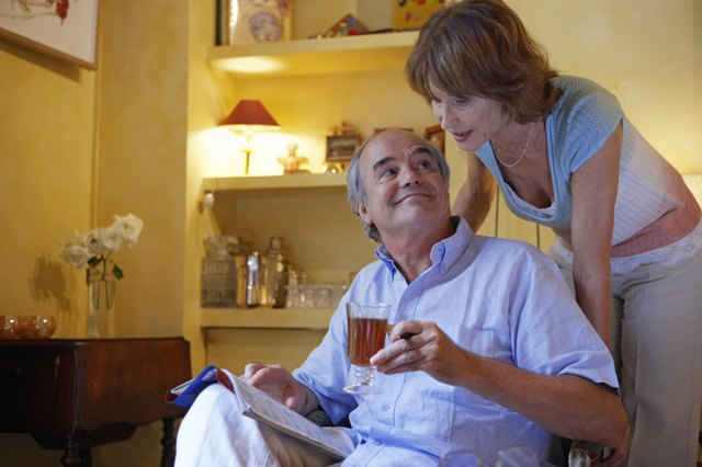 Mature couple relaxing in living room, woman at man's shoulder