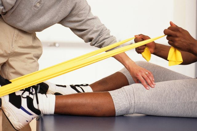 Man bending forward in physical therapy centre, woman supervising, surface view