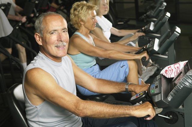 Mature man on cycling machine in gym, smiling, portrait