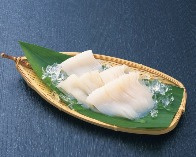 Fresh squid served on a bamboo basket with a leaf and ice cubes