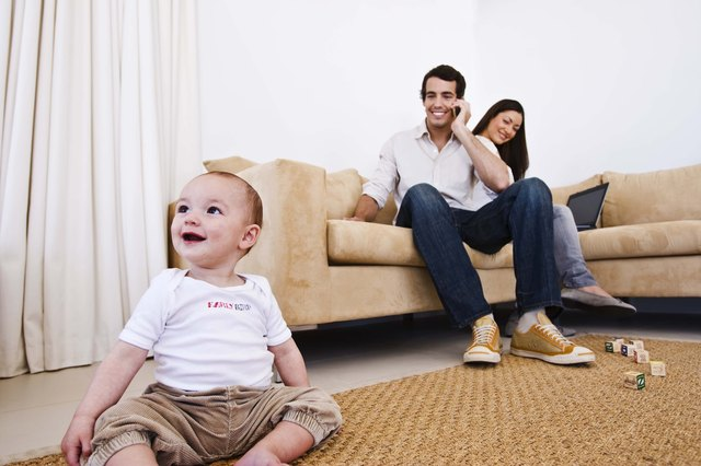 Mother on laptop computer, father on cell phone and baby sitting on floor