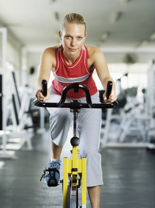 Portrait of a young woman on exercise bike in gym.