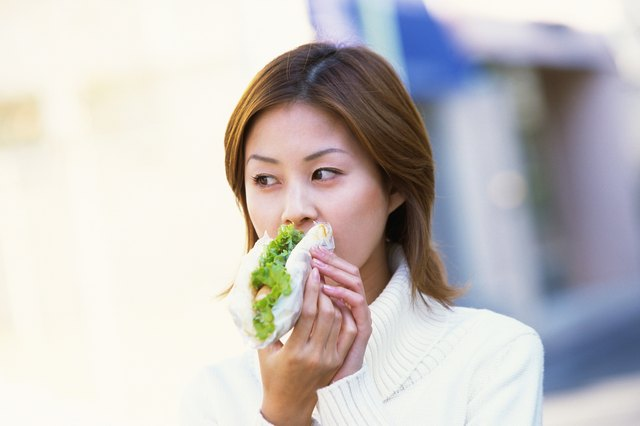 Young Adult Woman Eating a Sandwich, Front View