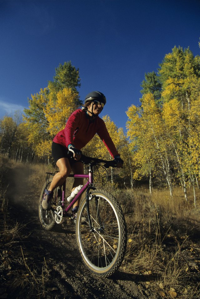 Female mountain biker riding on trail in forest
