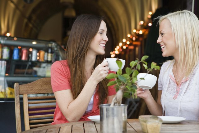 Women drinking coffee and chatting at cafe