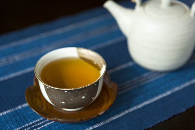 High Angle View of a Tea Cup Filled with Tea and a Tea Pot in the Background, Differential Focus, Close Up