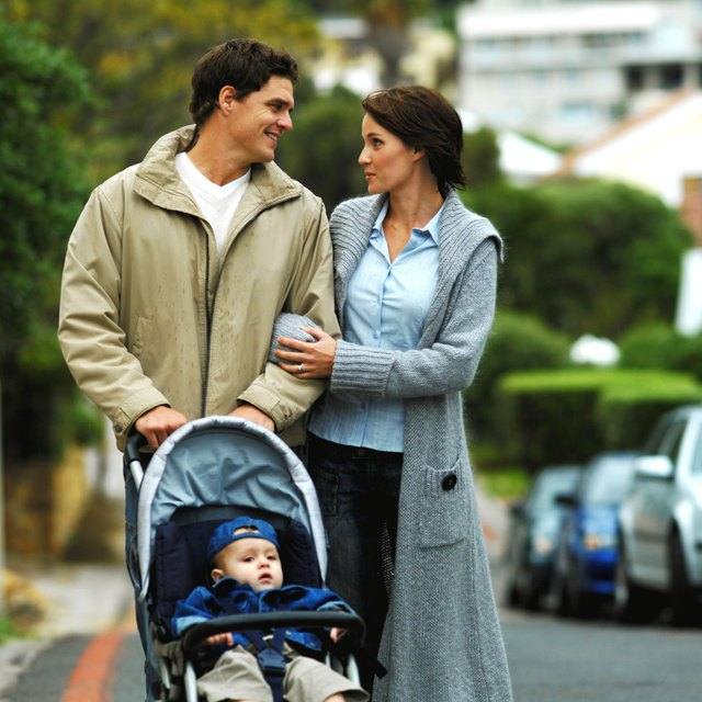 mother and father out walking with baby son (12-18 months) in buggy