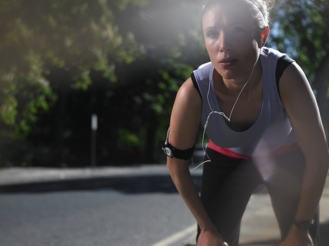 Young woman at street breathing heavily after jogging, lens flare