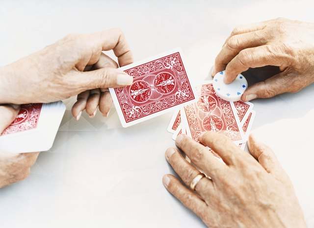 Close-Up on the Hands of a Senior Man and Woman Holding Playing Cards and Gambling Chips