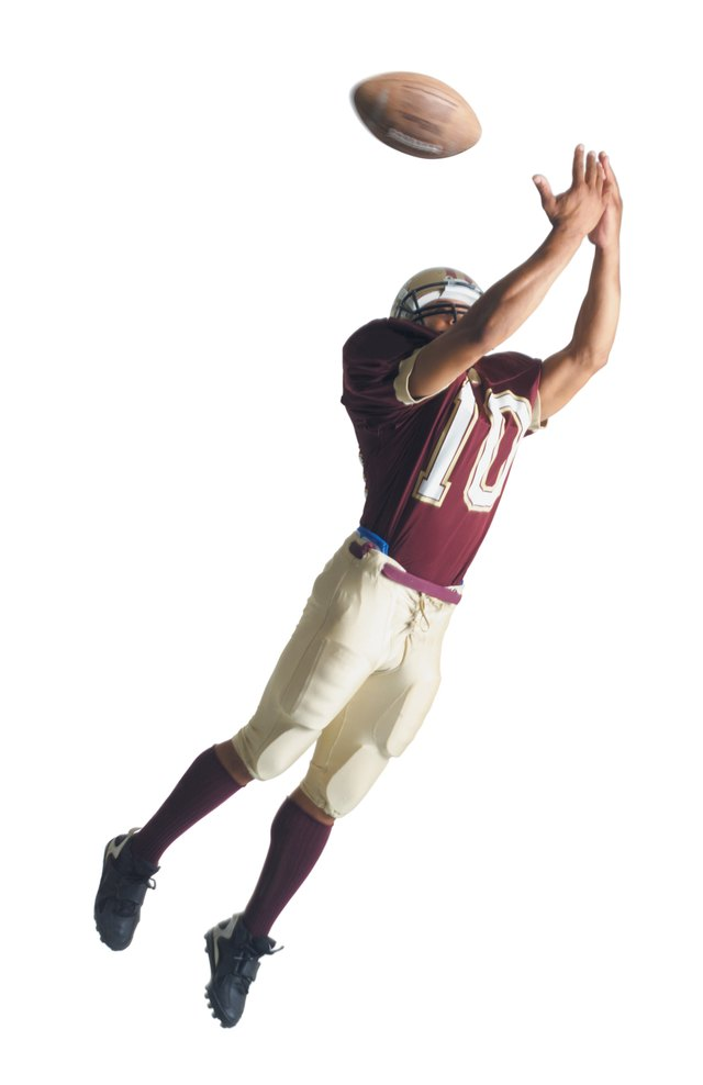 an african american football player in a red and white uniform is jumping up with arms outstretched to catch a football