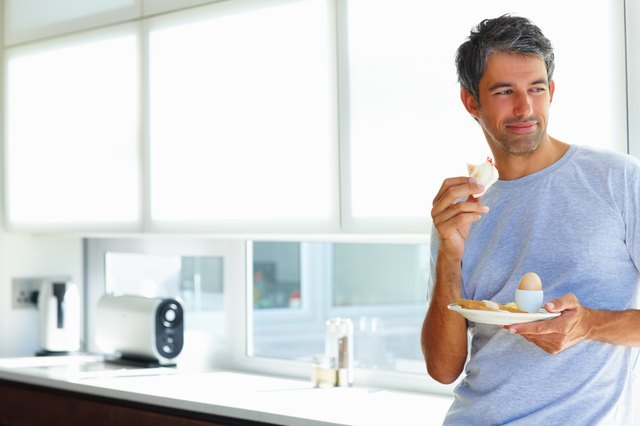 Mature holding his breakfast plate, thoughtful