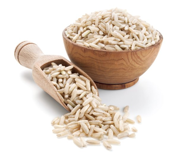 brown rice in a wooden bowl isolated on white