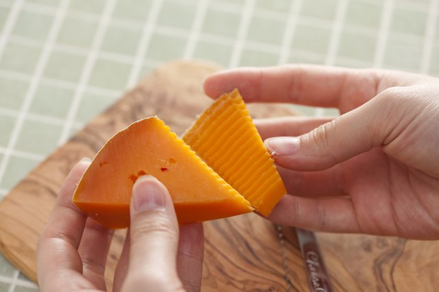 Hands pulling apart two pieces of cheese