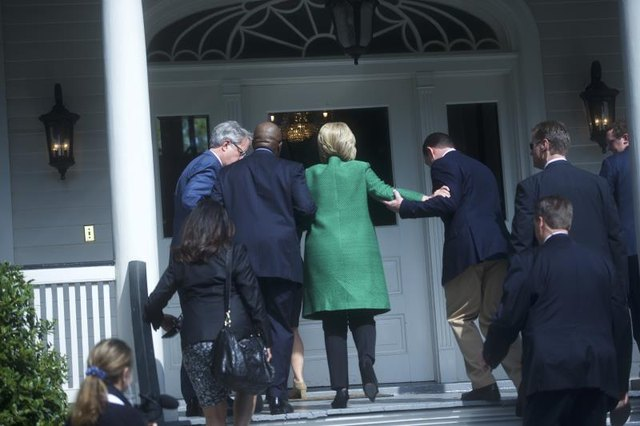 Campaign members assist Clinton up a small flight of steps.
