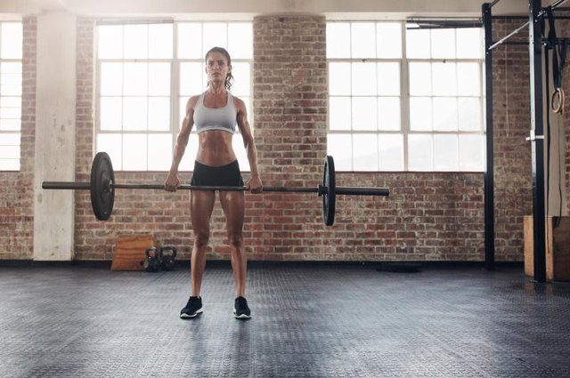 Full length portrait of muscular woman in a gym doing heavy weight exercises. Fitness female doing weight lifting at health club.