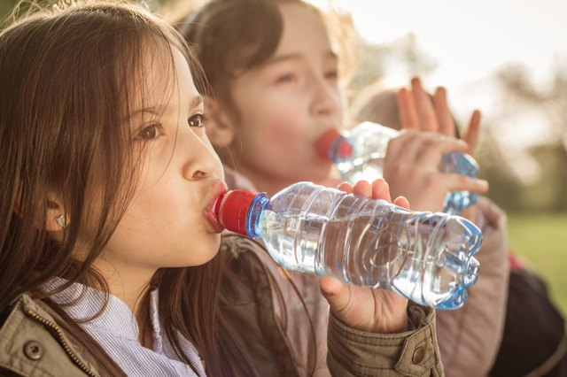 Photo of two girls drinking water from PET bottle