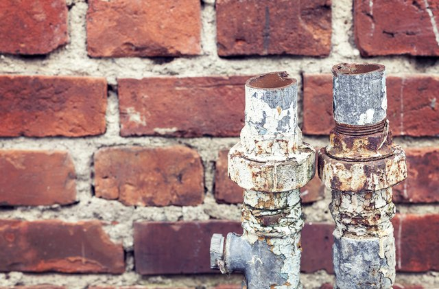 Old rusty cut pipes on a brick wall background.