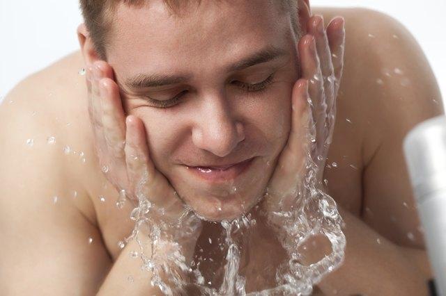 young man washing his face