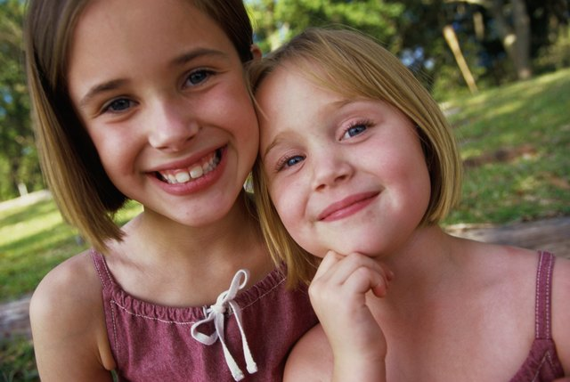 Portrait of two girls (4-5,8-9) smiling