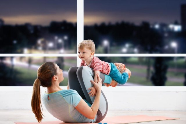Mother workout at fitness class in evening  with her baby