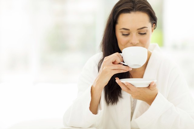 woman in bathrobe drinking coffee