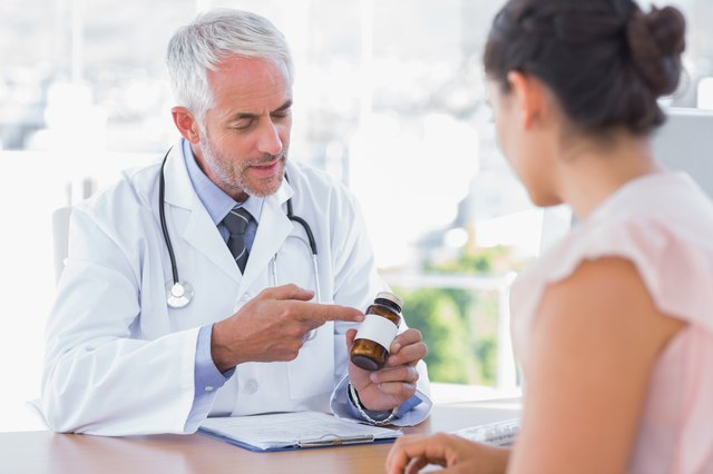 Doctor explaining the bottle of pills to patient